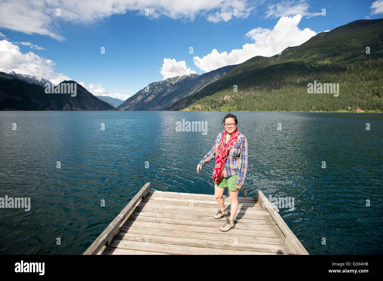 A woman on a dock at Anderson Lake,D'Arcy, near Pemberton, British Columbia.  Canada - Stock Image