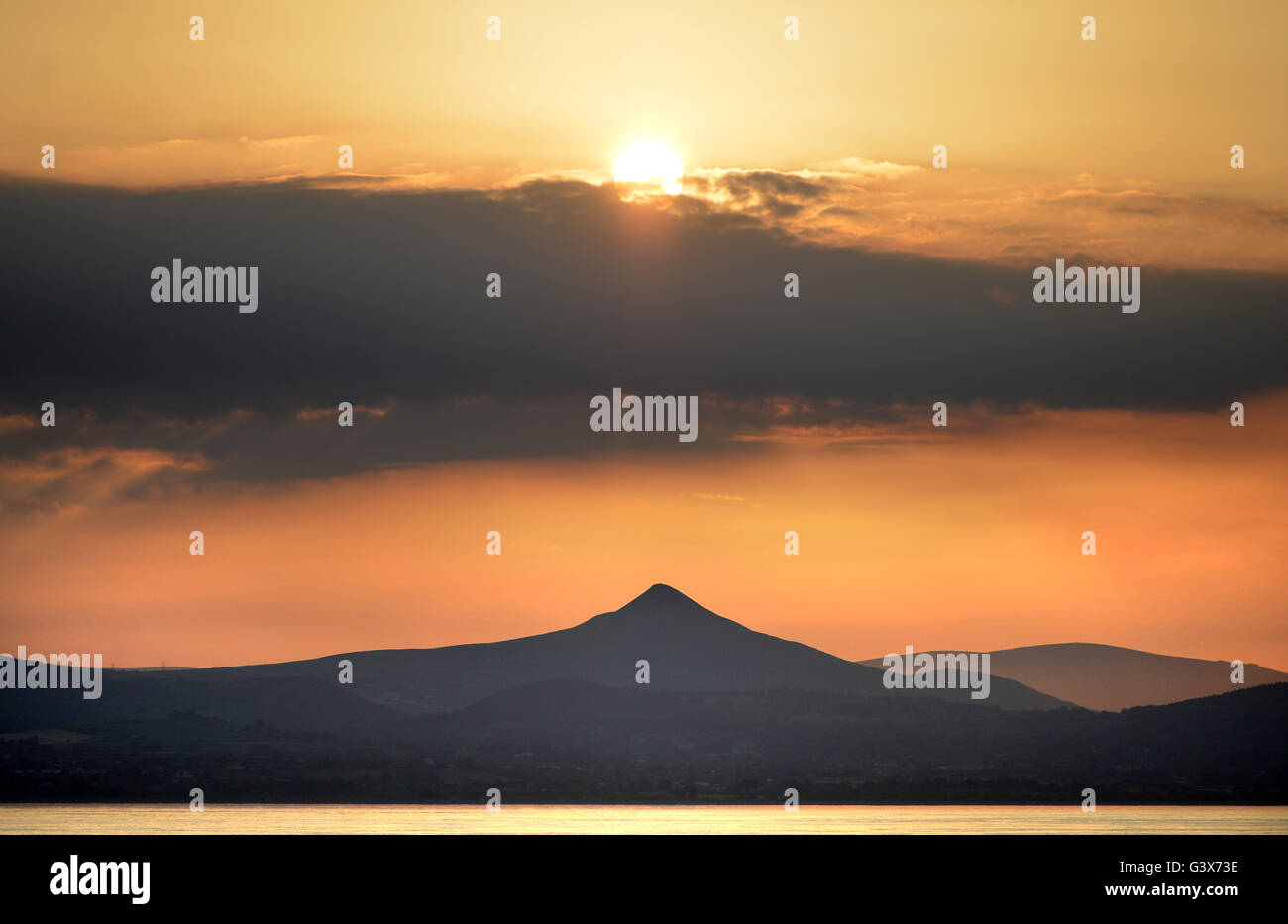Evening sun over Wicklow Mountains national Park, Leinster, Ireland with Great Sugar Loaf hill, taken from the Irish - Stock Image