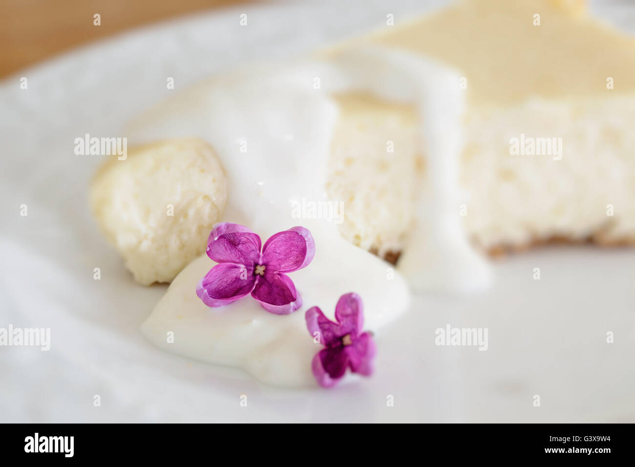 Lemon cheesecake decorated with individual lilac blooms. Intentional shallow depth of field with focus on the lilac - Stock Image