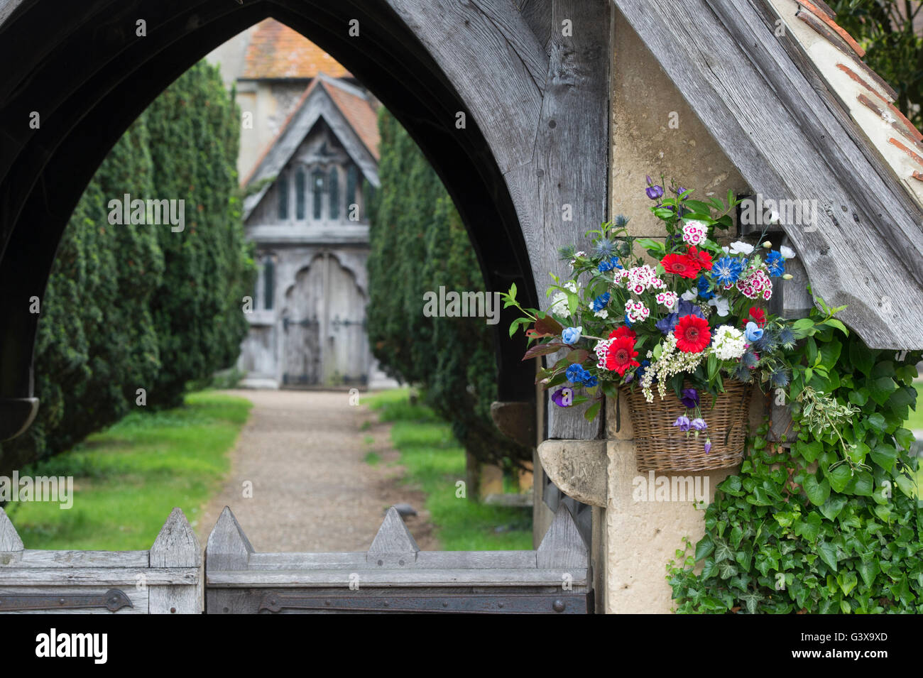 Flower basket on St Marys church lychgate. Hambleden, Buckinghamshire, England - Stock Image