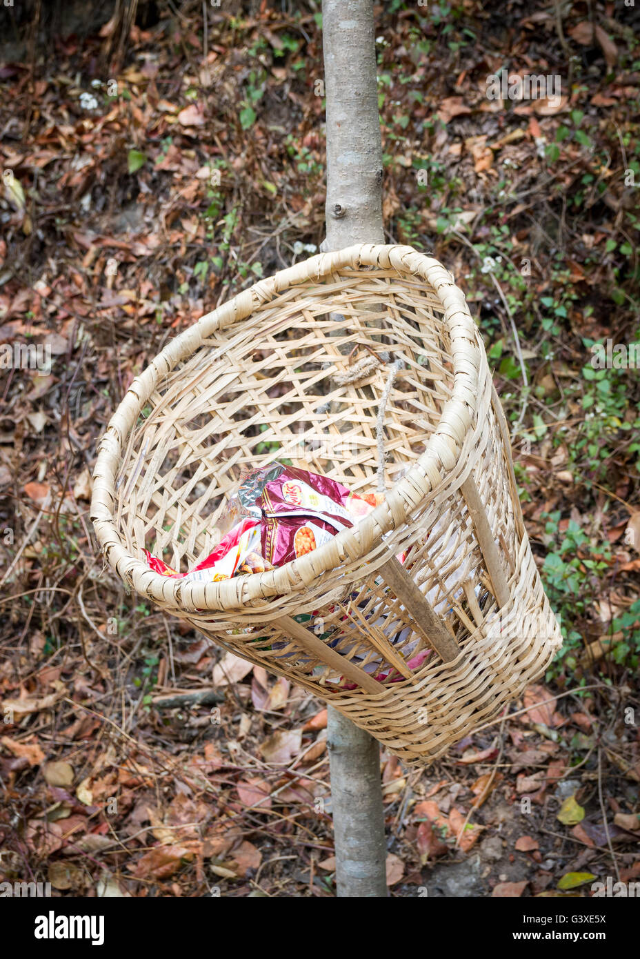 Unique handmande bamboo basket or dustbin placed on the streets of rural Nepalese Village. - Stock Image