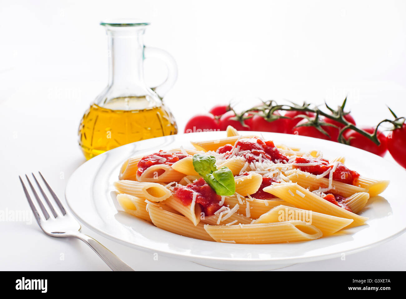 Plate of penne pasta with tomato sauce and parmesan cheese. - Stock Image