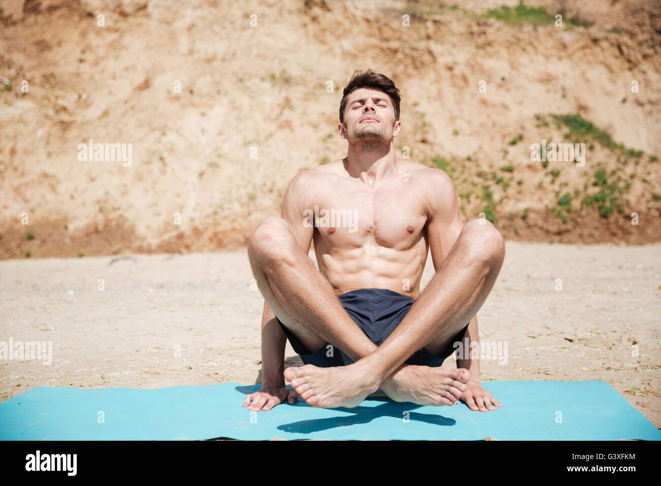 Relaxed handsome young man practicing yoga on the beach - Stock Image