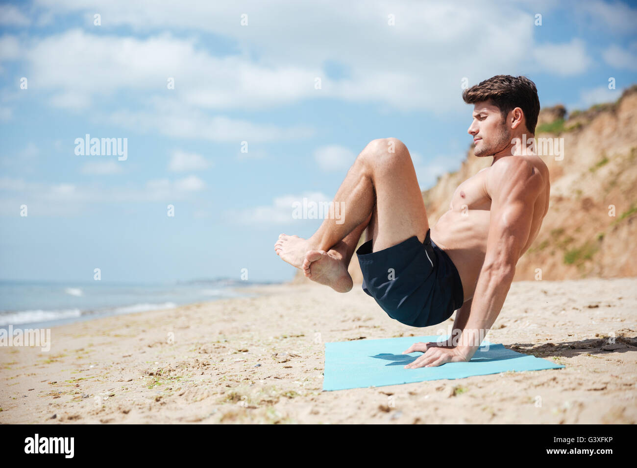 Man with eyes closed balancing on his hands and practicing yoga on the beach - Stock Image