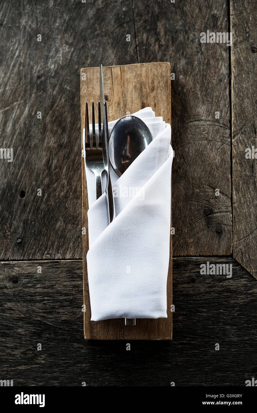 chic cutlery on old rustic wooden casual restaurant table - Stock Image