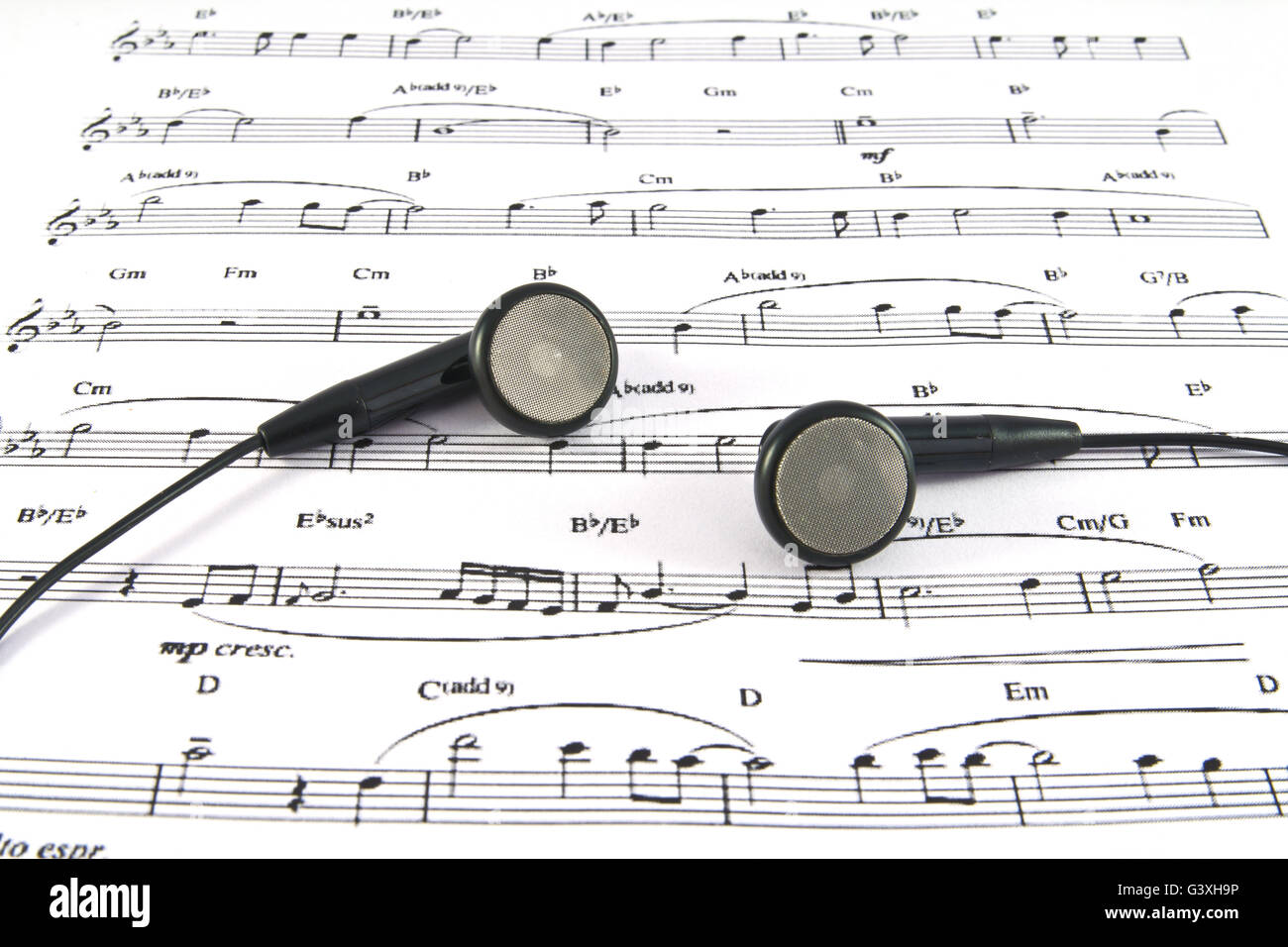 An ear phone on the top of a music sheet - Stock Image