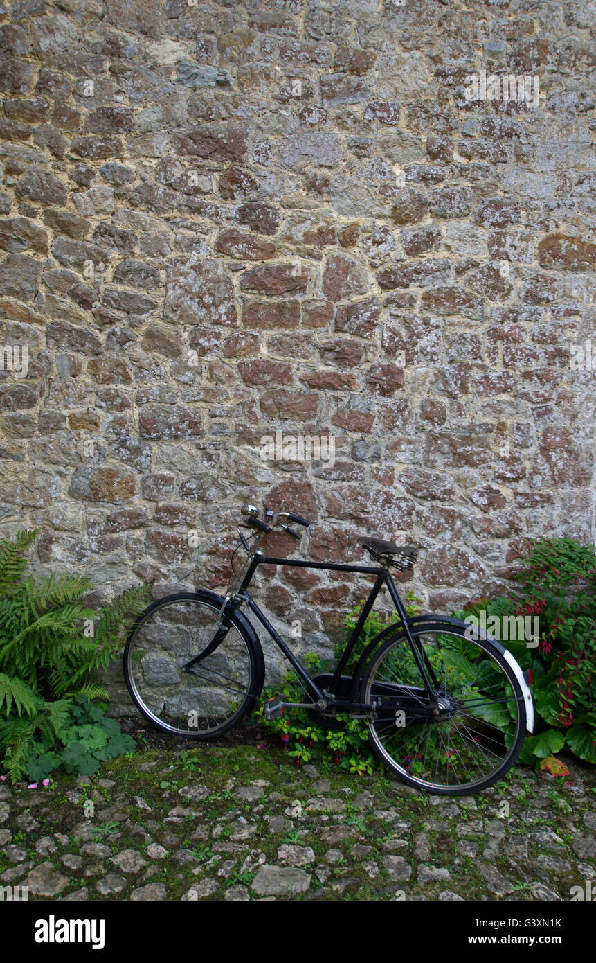 Vintage black bicycle against a stone wall. - Stock Image