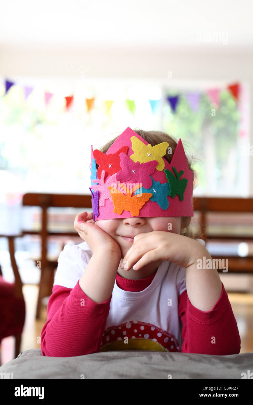 Young girl in a party hat covering her eyes - Stock Image