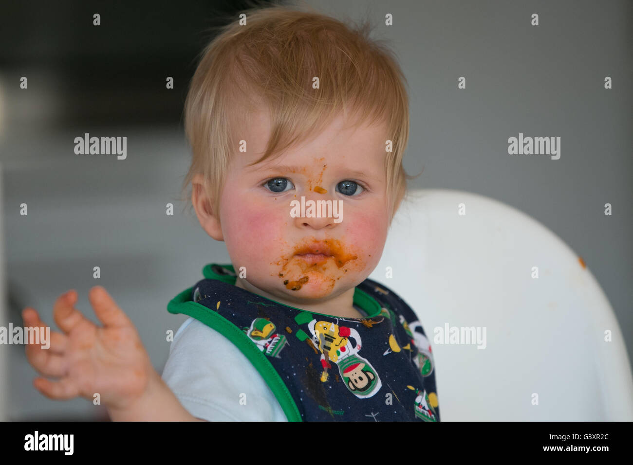 Toddler getting messy whilst eating dinner - Stock Image