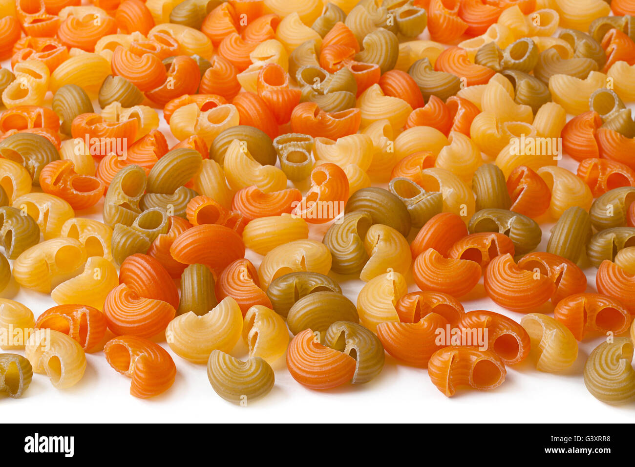 Multicolor dry swirl pasta closeup background - Stock Image