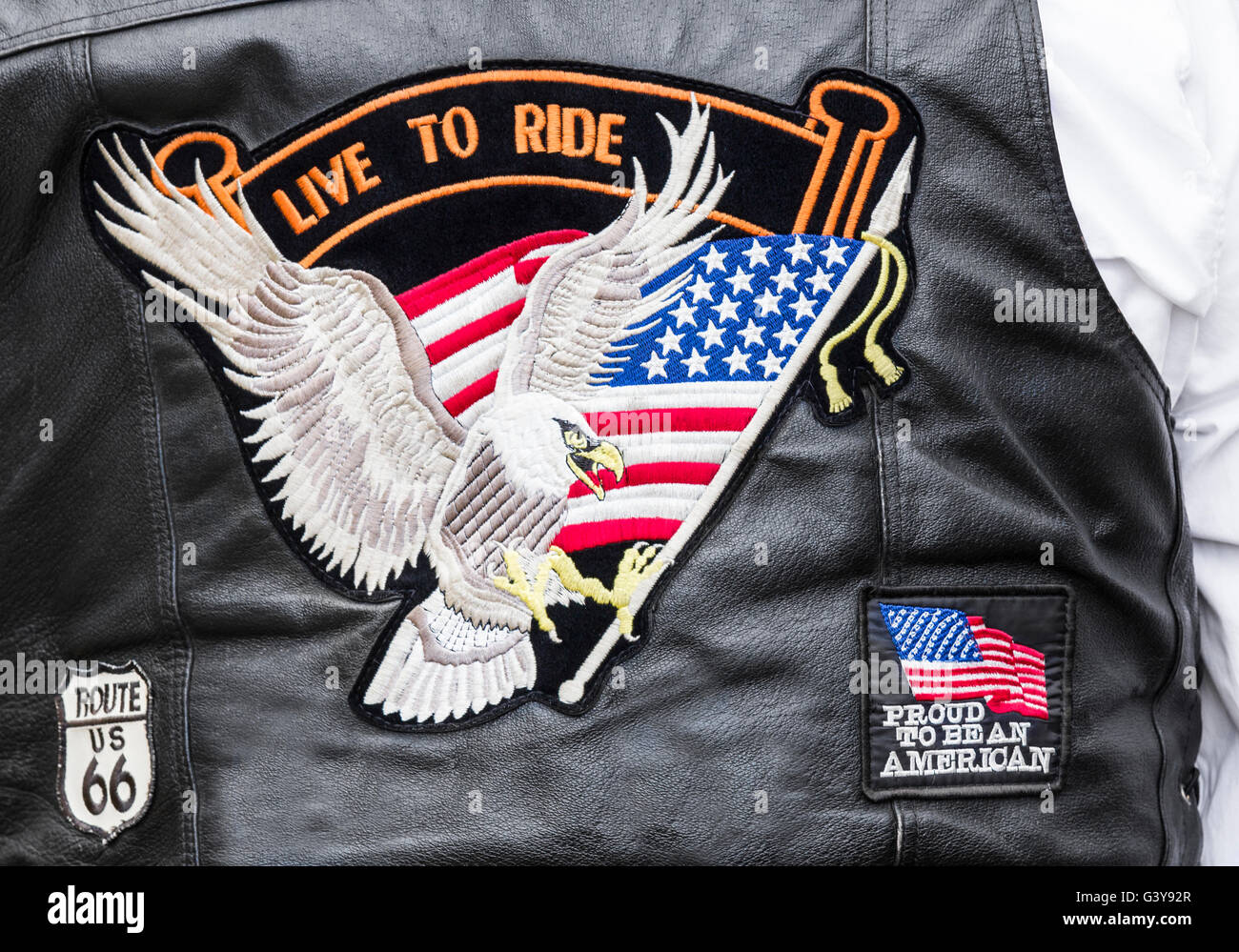 Biker wearing 'Live to ride', 'proud to be an American' and 'Route 66' badges on back of - Stock Image