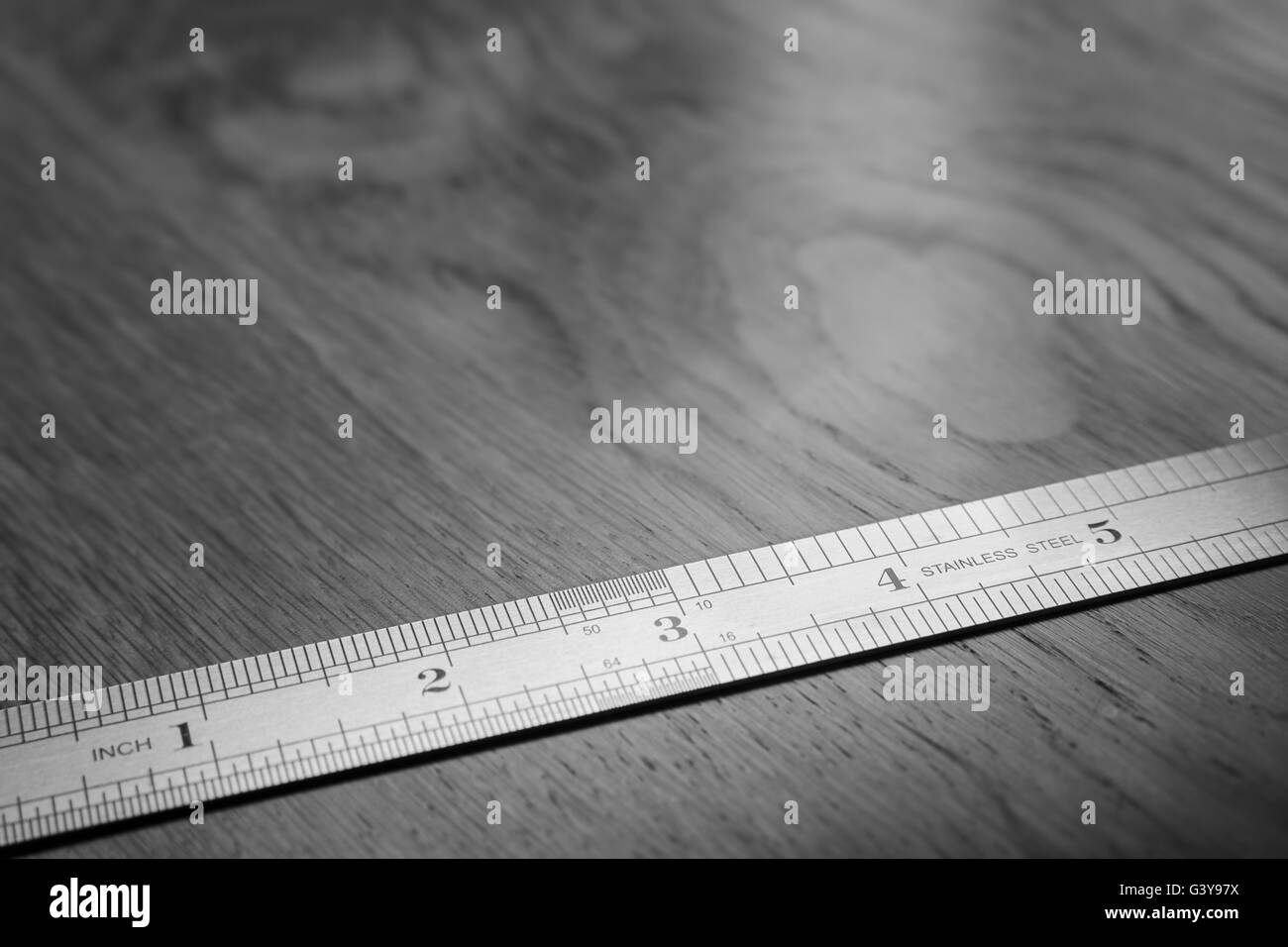 Meral ruler on wooden table. Metric and inches. - Stock Image