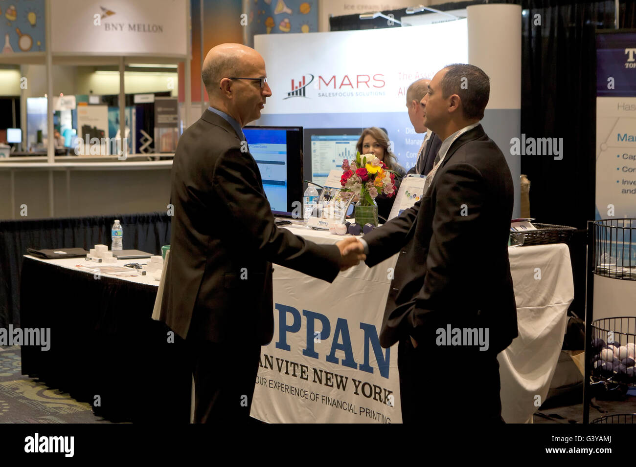 Businessmen shaking hands at an business expo exhibit - Washington, DC USA - Stock Image