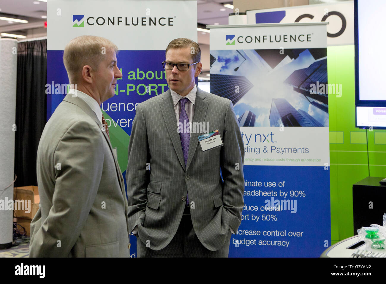 Representatives of Confluence Technologies await clients at a business expo - USA - Stock Image