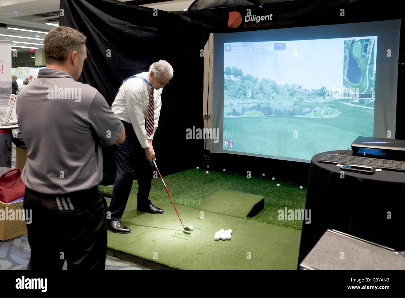 businessman teeing off at a golf simulator - USA - Stock Image