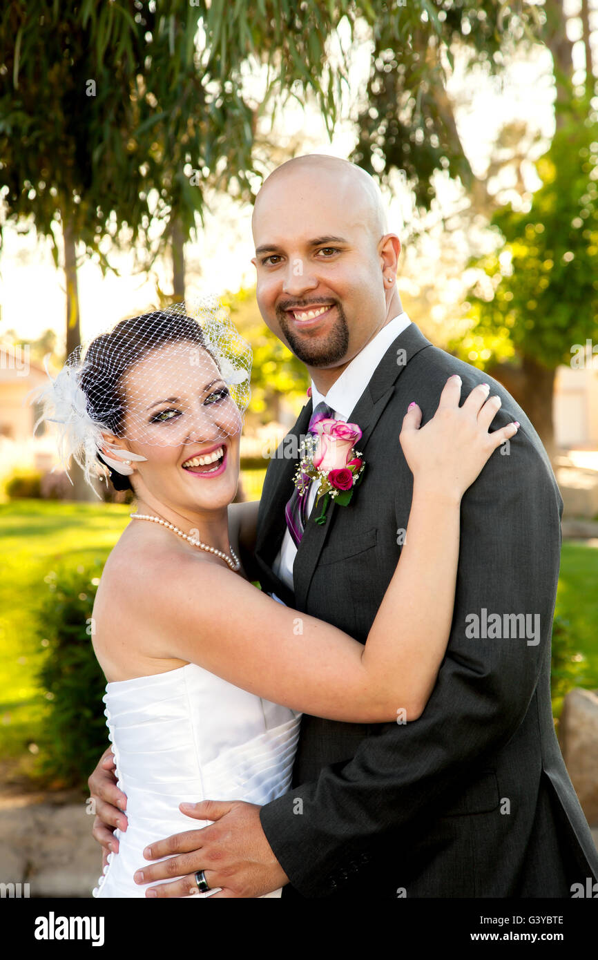 A bride and groom hold each other and laugh while looking at the camera.  They are happy and posed but unposed at - Stock Image