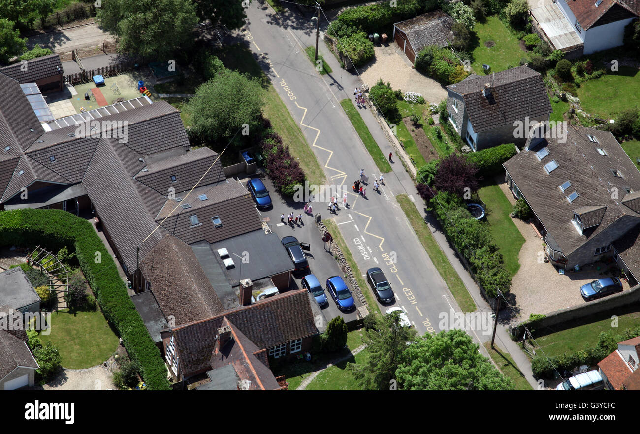aerial view of a Primary school with supervised children crossing the road, UK - Stock Image