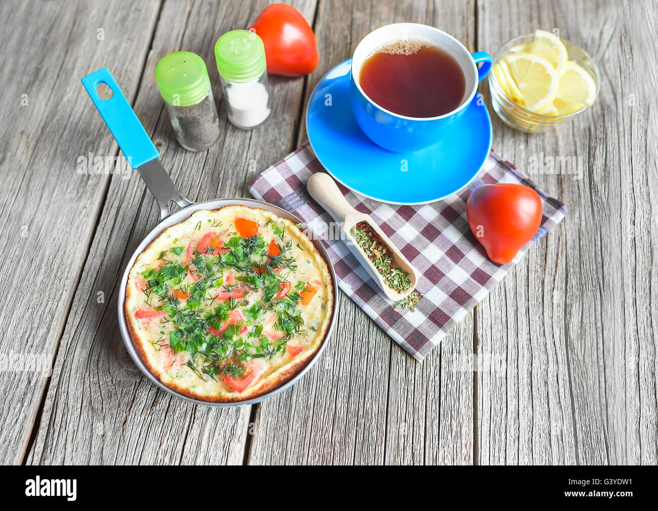 Omelet with vegetables in a frying pan on a wooden table. - Stock Image