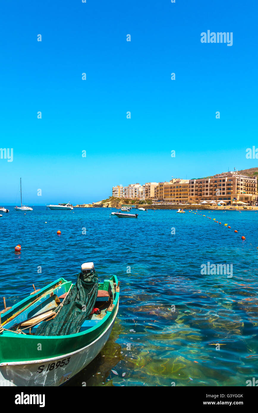 Fishing boat moored in Marsalforn Bay and panorama of the most popular and largest summer resort - Marsalforn, Gozo, - Stock Image