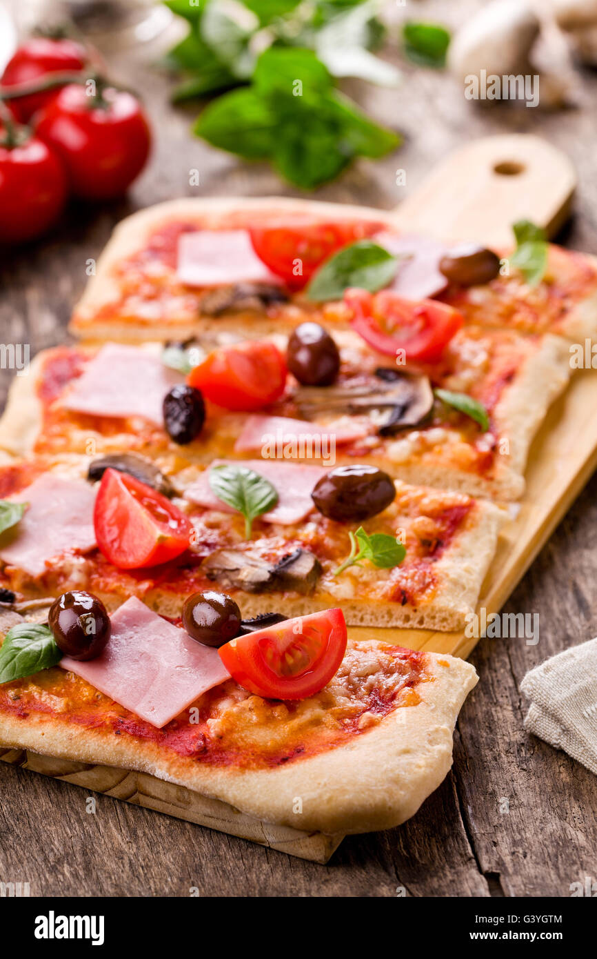 Homemade pizza with fresh tomatoes olives and mushrooms - Stock Image