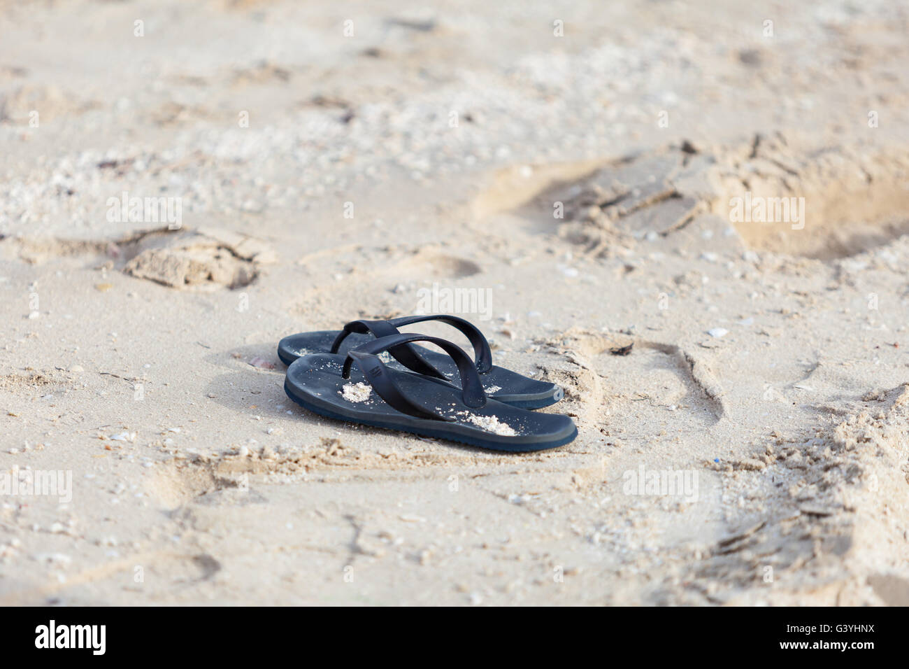 Flip flops, thongs, slides,  abandoned on sandy beach by the sea - Stock Image
