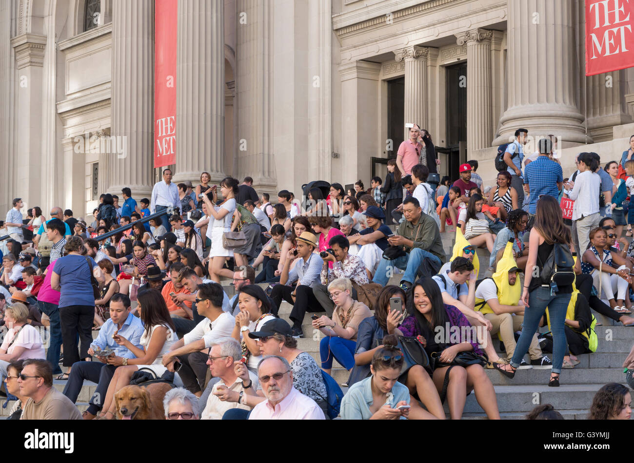 Crowd of people sitting on the steps of the Metropolitan Museum of Art, New York City. - Stock Image