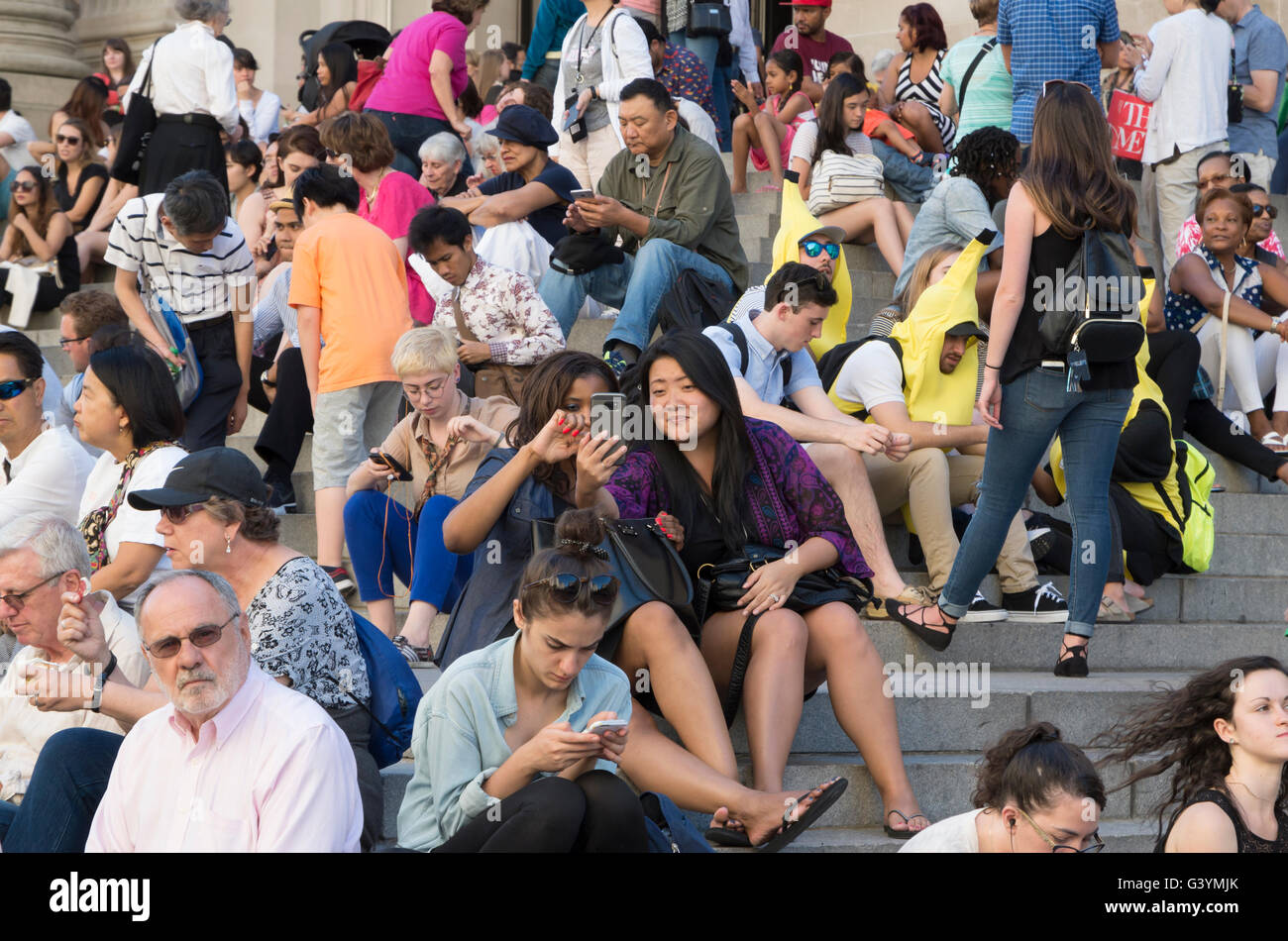 Crowd of people sitting on steps with focus on two girls taking a selfie. - Stock Image