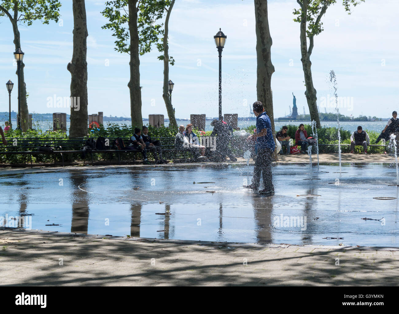 Teenage boys keeping cool in Summer by running through a public water fountain and messing about in Battery Park, - Stock Image