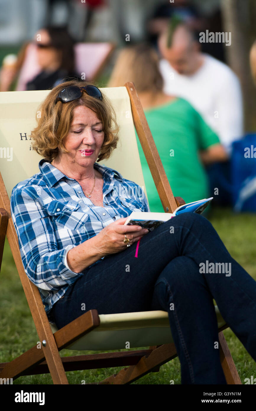 A woman sitting in a deckchair reading a book  visiting attending enjoying  the warm sunshine  at  the Hay Festival - Stock Image