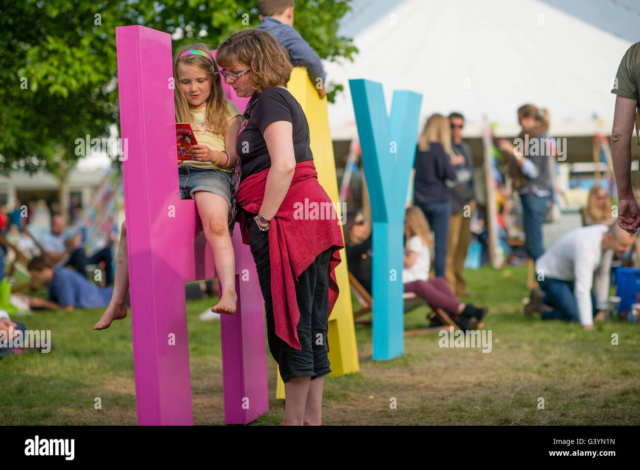 A mother and child daughter girl  visiting attending enjoying themselves with one of the big signs at  the Hay Festival - Stock Image
