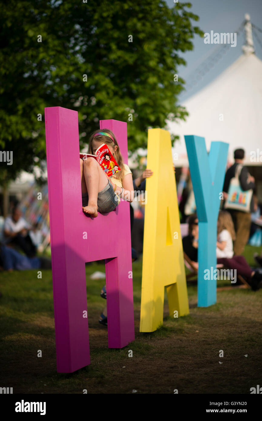 People visiting attending enjoying themselves with one of the big signs at  the Hay Festival of literature and the - Stock Image