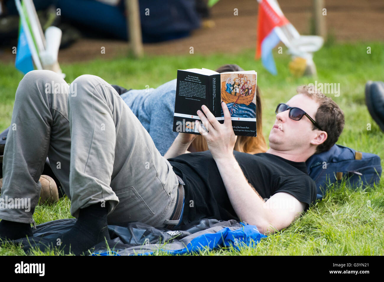 A man lying on his back reading a book  visiting attending enjoying themselves in the warm sunshine  at  the Hay - Stock Image