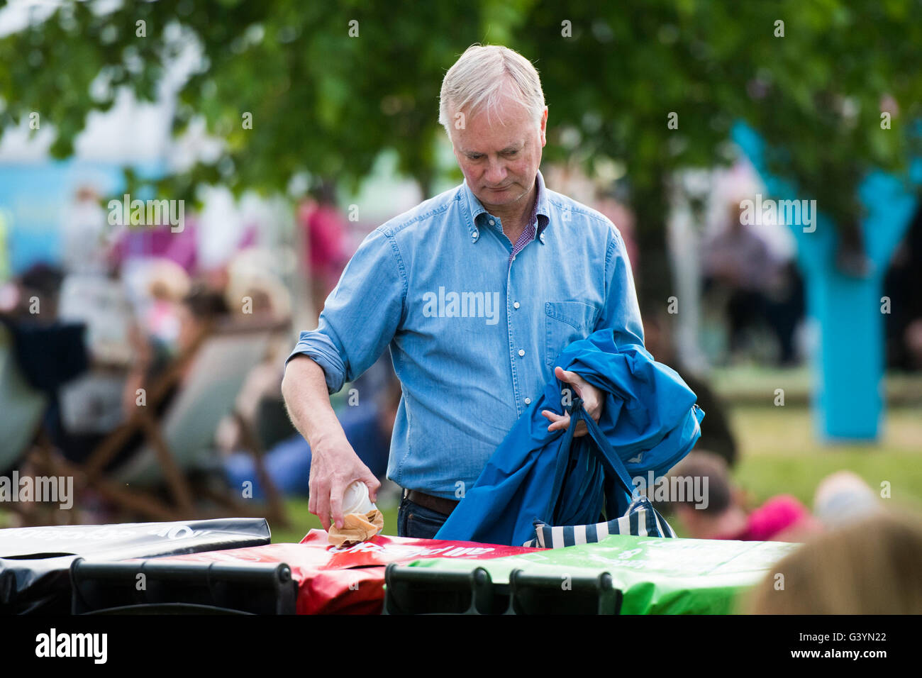A man looking to recycle his rubbish trash waste  at  the Hay Festival of literature and the arts , Hay on Wye, - Stock Image
