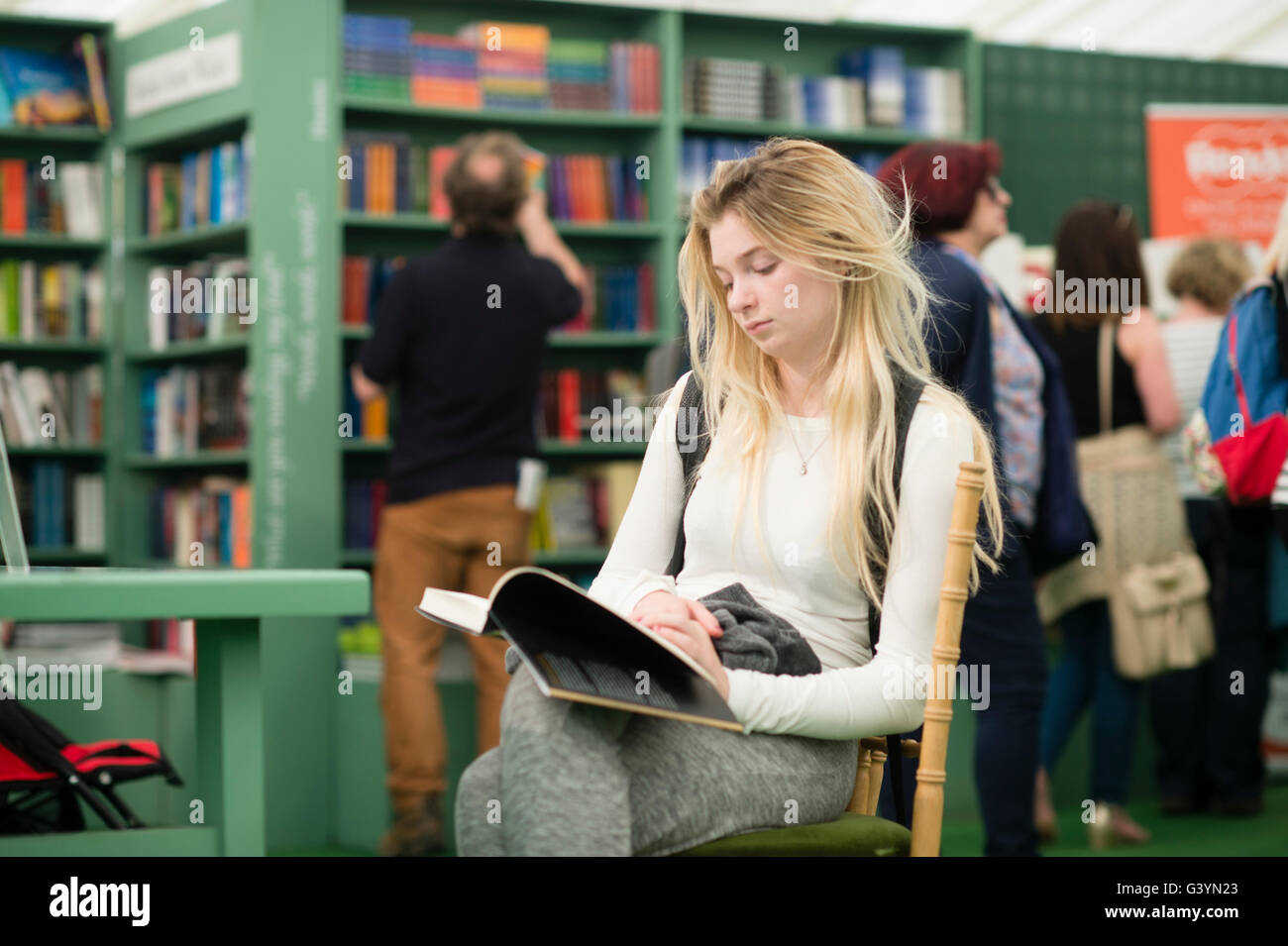 A young woman reading a book  visiting attending enjoying the Hay Festival of literature and the arts , Hay on Wye, - Stock Image
