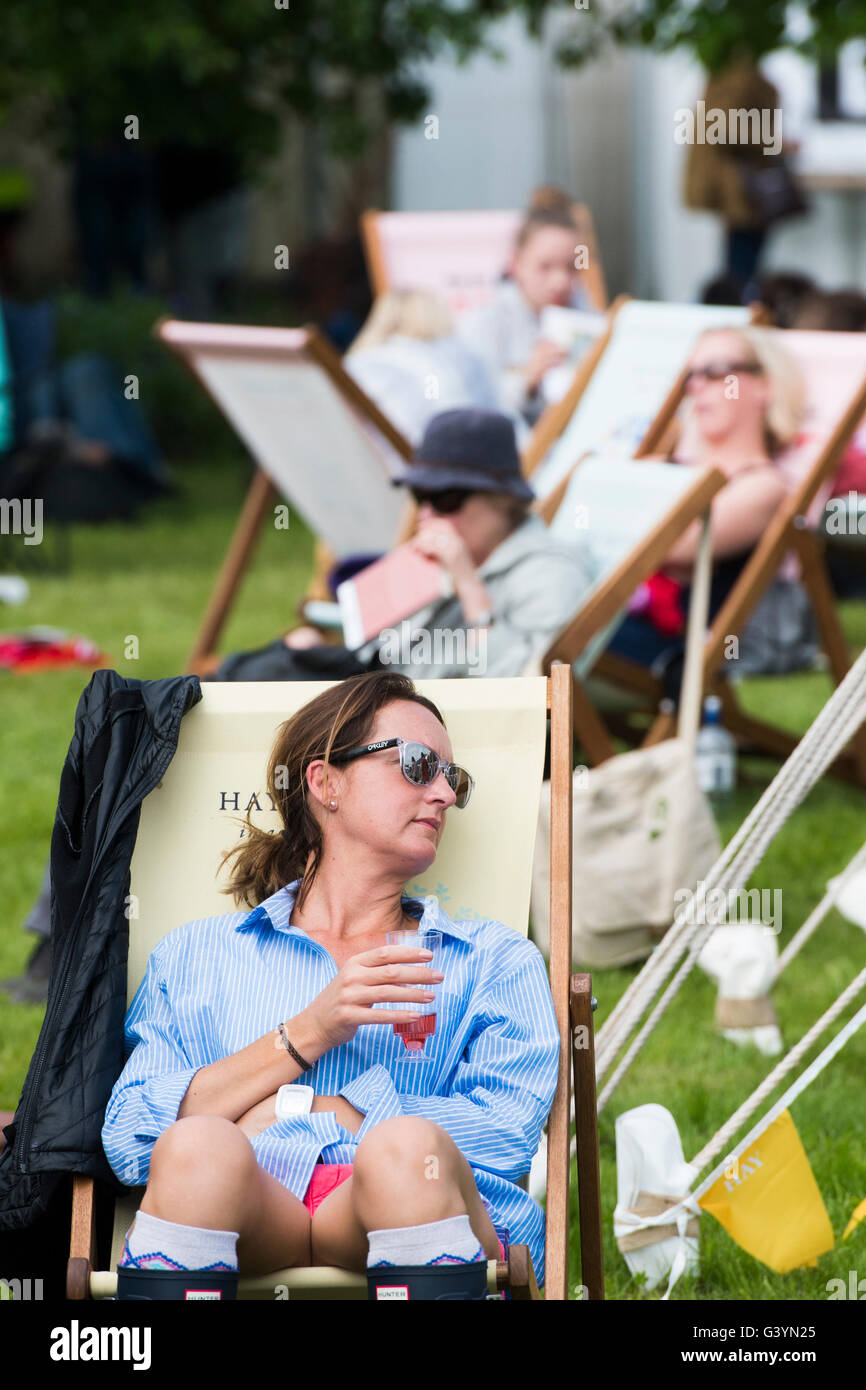 People sitting in deckchairs visiting attending enjoying themselves in the warm sunshine  at  the Hay Festival of - Stock Image