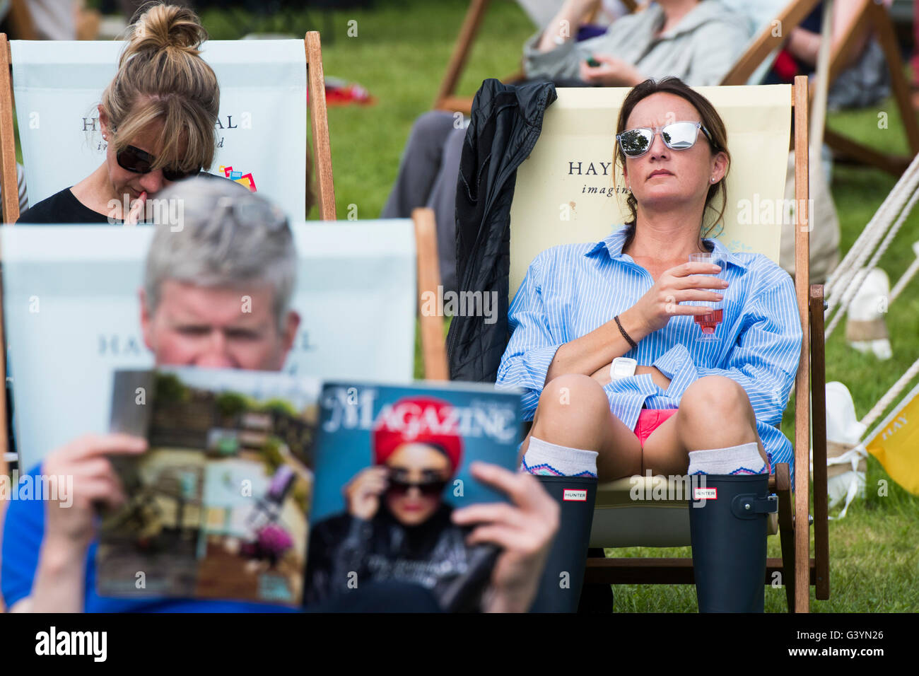 People visiting attending enjoying themselves in the warm sunshine  at  the Hay Festival of literature and the arts - Stock Image