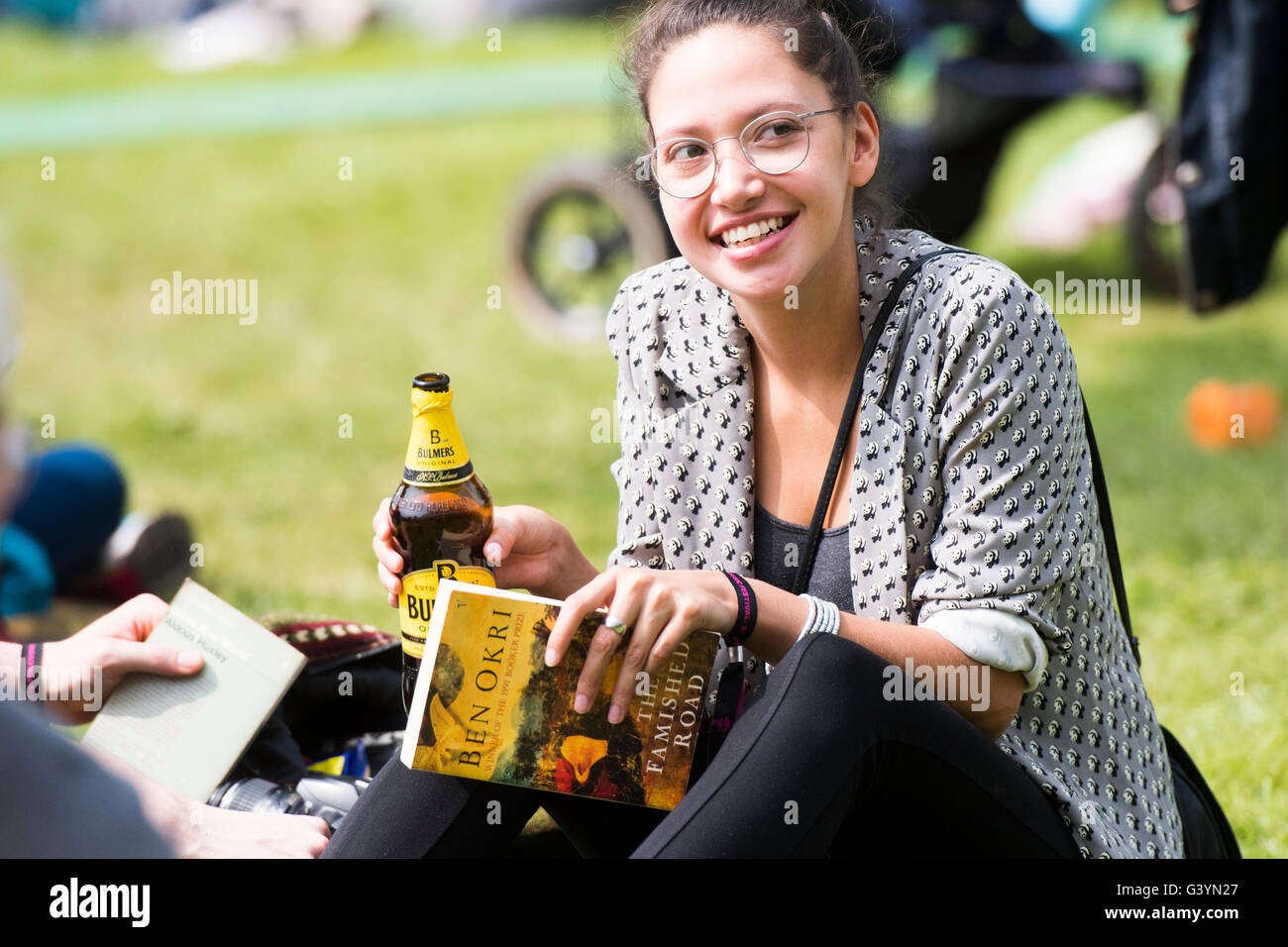 A woman  visiting attending enjoying herself with a bottle of cider  in the warm sunshine  at  the Hay Festival - Stock Image