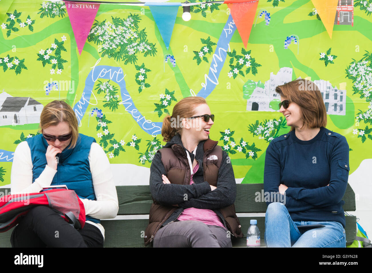 Three women  visiting attending enjoying themselves in the warm sunshine  at  the Hay Festival of literature and - Stock Image