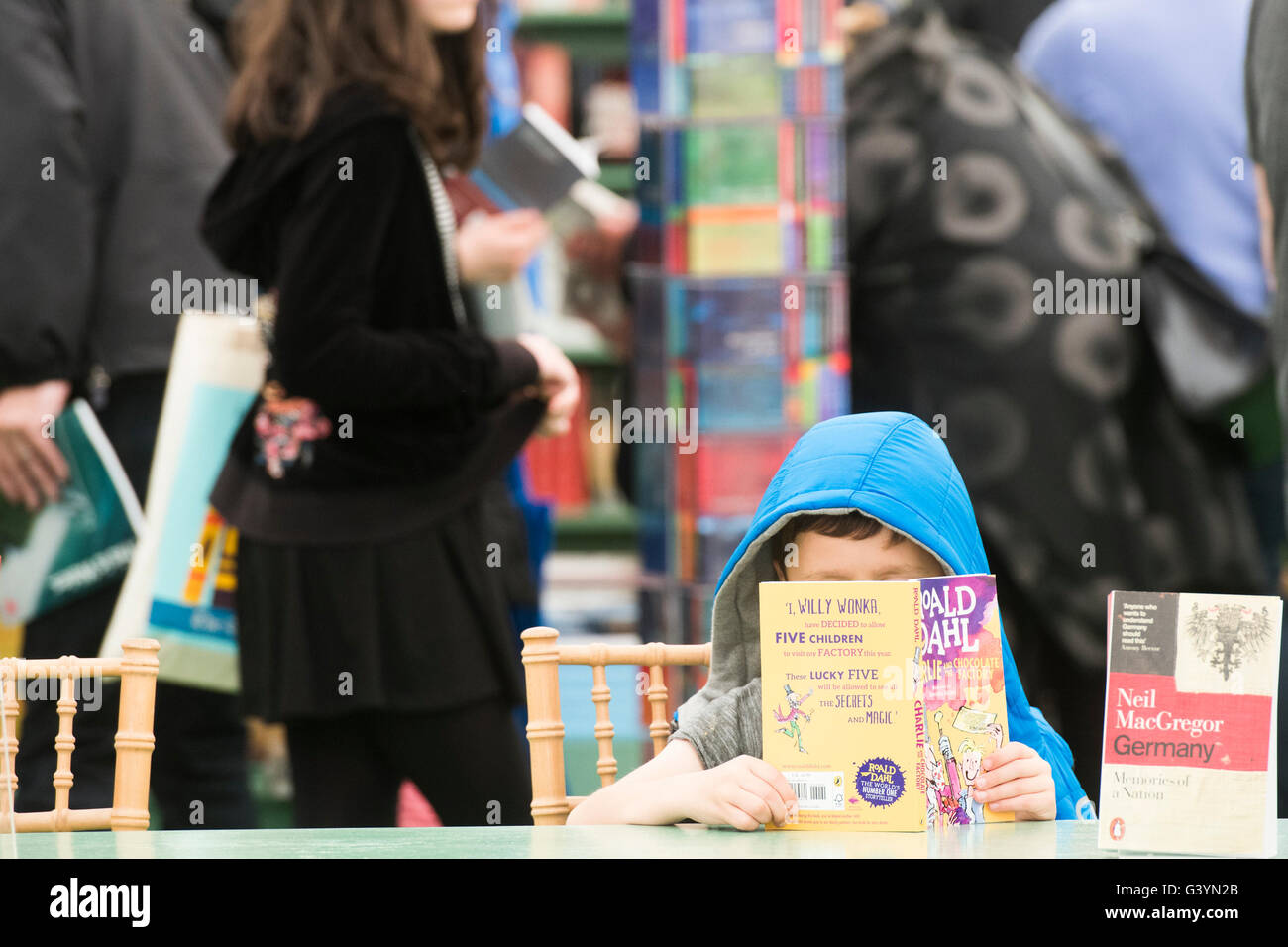 A small boy reading a book at  the Hay Festival of literature and the arts , Hay on Wye, Powys, Wales UK, May 2016 - Stock Image