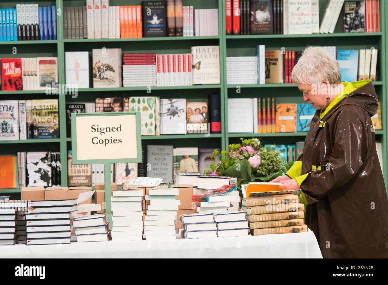 A woman reading a book inthe festival bookshop at  the Hay Festival of literature and the arts , Hay on Wye, Powys, - Stock Image