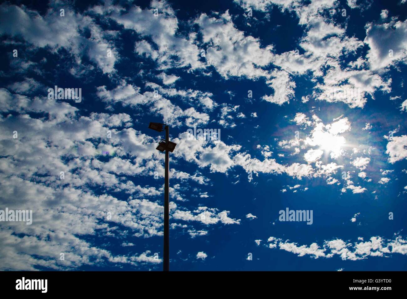 deep Blue sky with white fluffy clouds and a single street light - Stock Image