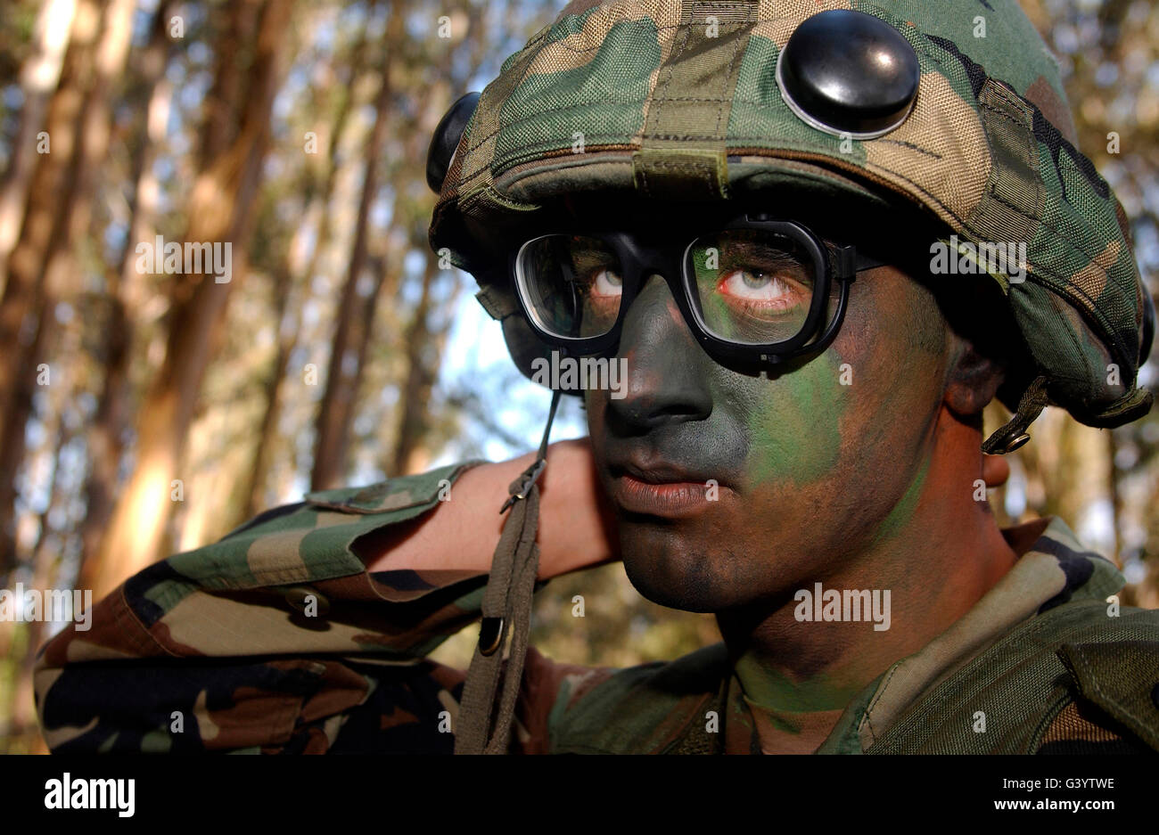 Airman applies camouflage make-up. - Stock Image