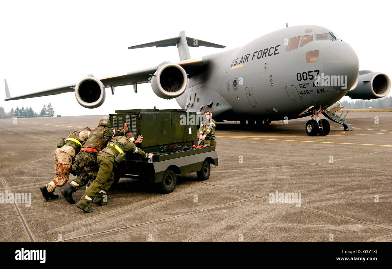 Airmen push a diesel generator in place after the C-17 Globemaster III lands. - Stock Image