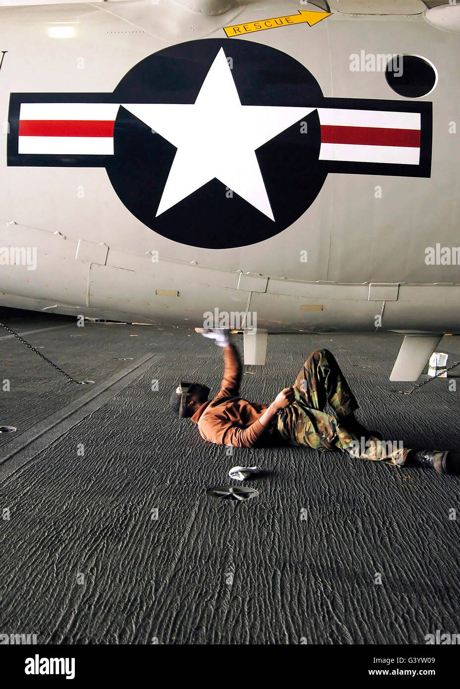 Airman cleans the underside of an E-2C Hawkeye. - Stock Image
