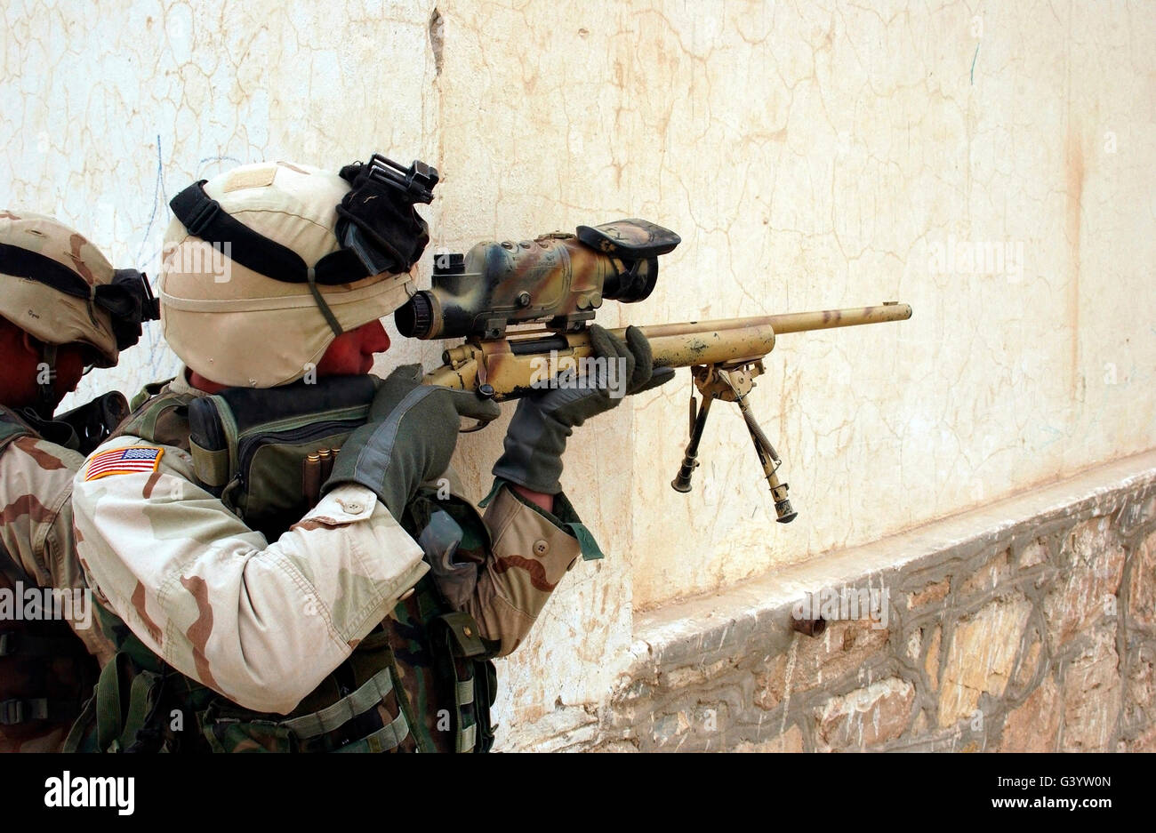 U.S. Army Sniper sights through his scope on his Harris M-86 sniper rifle. - Stock Image