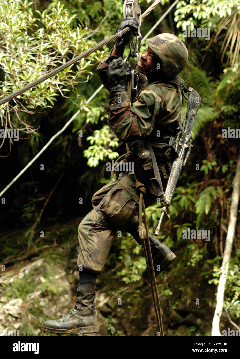 A soldier slides across a river using a pulley system. - Stock Image