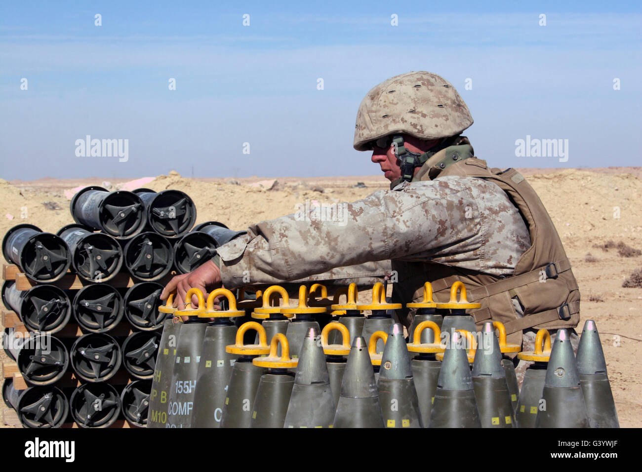 Ammunition team prepares 155 mm high-explosive artillery rounds. - Stock Image