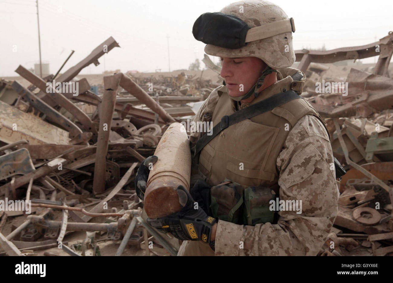 A soldier carries an unused 155 millimeter artillery round. - Stock Image