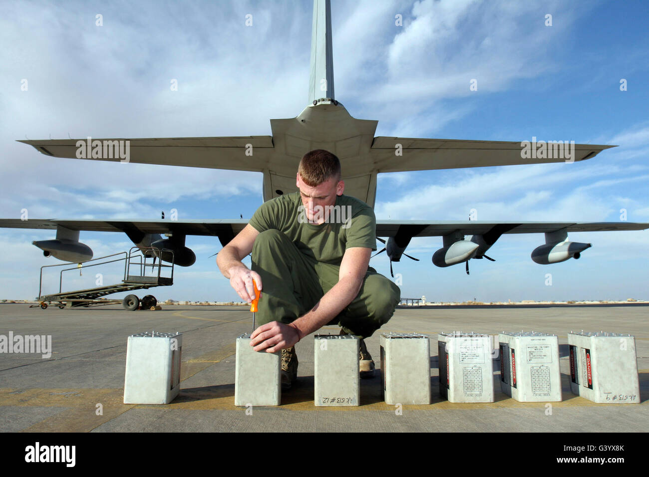 A marine replaces flares in flare dispensers from a KC-130J Hercules. - Stock Image