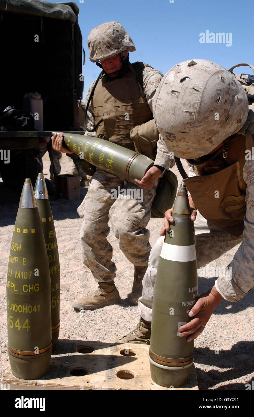 Artillerymen stage 155-millimeter rounds atop a wood crate. - Stock Image
